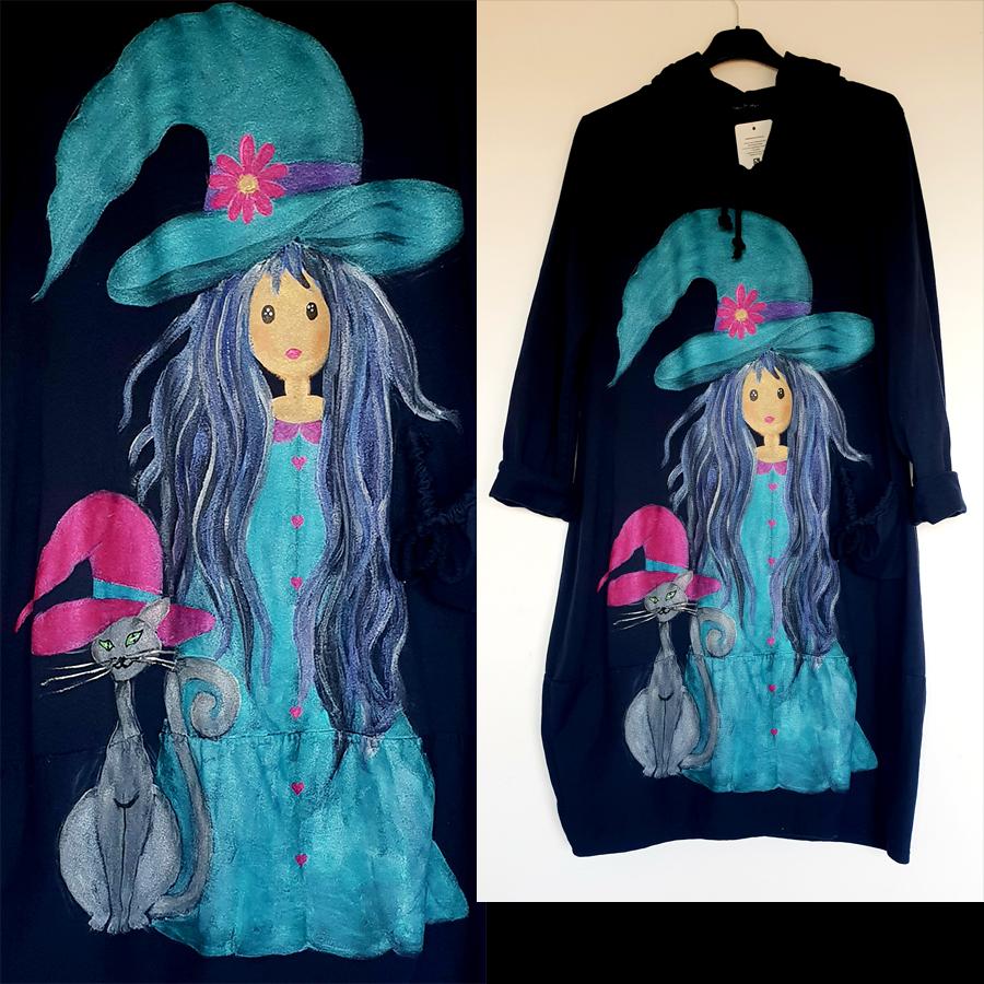 Dekle čarovnica s klobukom na špic na črni obleki.